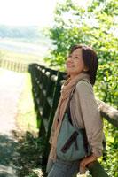 林道に立って微笑むシニア女性
