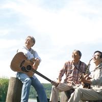 湖の岸辺で楽器を持って青空を見上げる3人のシニア男性