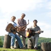 湖の岸辺で楽器を持つ3人のシニア男性