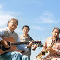 青空をバックに楽器を演奏する3人のシニア男性