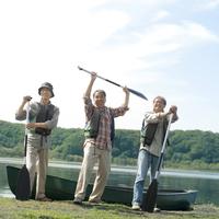 カヌーの前でオールを持って立つシニア男性3人