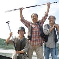 湖の岸辺でオールを持って立つシニア男性3人