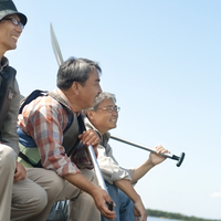 湖の岸辺でオールを持って微笑むシニア男性3人の横顔