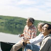 湖の岸辺で空を見上げ微笑むシニア男性3人の横顔