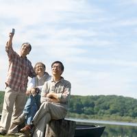 湖の岸辺でカヌーに座るシニア男性3人