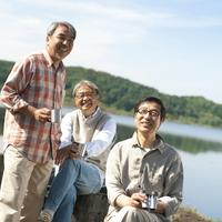 湖の岸辺でコーヒーを手に微笑むシニア男性3人