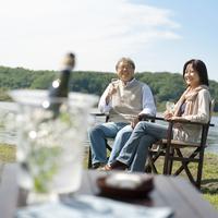 湖の岸辺でワインを飲むシニア夫婦 20027006048| 写真素材・ストックフォト・画像・イラスト素材|アマナイメージズ