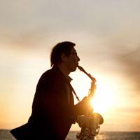 夕日のバックにサックスを演奏するシニア男性のシルエット