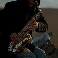砂浜でサックスを演奏するシニア男性の手元