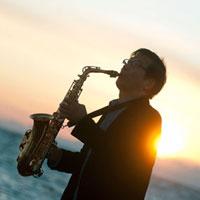夕暮れの海辺でサックスを演奏するシニア男性のシルエット