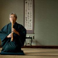 和室で尺八を吹く着物姿のシニア男性