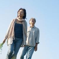 青空をバックに野花を持ち散歩するシニア夫婦