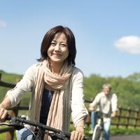 自転車に乗り微笑むシニア女性とシニア男性