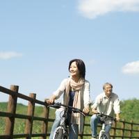 サイクリングロードで自転車に乗り微笑むシニア夫婦