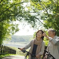 林道で自転車を止め微笑むシニア夫婦