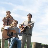 湖の岸辺で歌を歌う3人のシニア男性