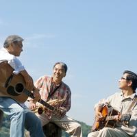 湖の岸辺で楽器を持って談笑する3人のシニア男性