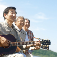 湖の岸辺で楽器を持って空を見上げる3人のシニア男性
