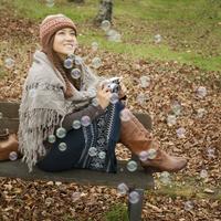 秋の公園のベンチでカメラを持ち微笑む20代女性とシャボン玉 20027006210| 写真素材・ストックフォト・画像・イラスト素材|アマナイメージズ