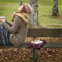 秋の公園のベンチに座り空を見上げる20代女性