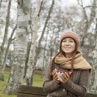 秋の公園のベンチに座りカフェオレボウルを持つ20代女性