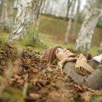 本を持ち落ち葉の上に寝転ぶ20代女性