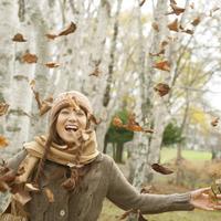 落ち葉を舞い上がらせ微笑む20代女性