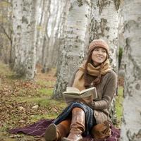 木に寄りかかり本を読む20代女性