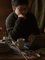 釣り道具のあるテーブルでパソコンを使う30代の男性