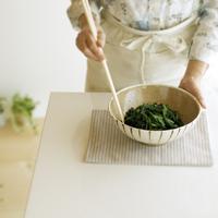 ホウレン草のゴマ和えを作るシニア女性の手元