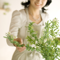 花を生け微笑むシニア女性