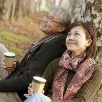 公園の木に寄りかかりコーヒーを飲むシニア夫婦