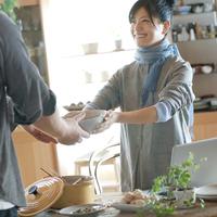 キッチンで料理を渡して微笑む20代女性