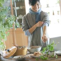 キッチンで腕まくりをしながら食事の準備をする20代女性