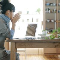 音楽を聴きながらノートパソコンを見る20代女性の横顔