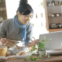 ノートパソコンでレシピを見ながら料理を作る20代女性
