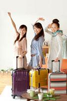 スーツケースを持ち旅行に出掛ける3人の20代女性