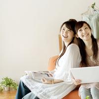 ソファーに座り微笑む2人の20代女性