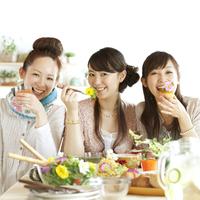 エディブルフラワーを使った料理を食べる3人の20代女性