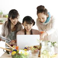 ノートパソコンの画面を見て驚く3人の20代女性