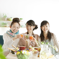 野菜ジュースで乾杯をする3人の20代女性