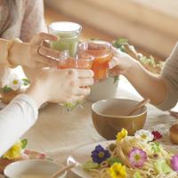 野菜ジュースで乾杯をする3人の20代女性の手元