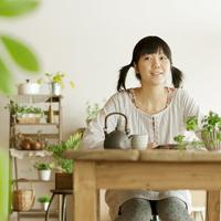 焼き芋とお茶を前に微笑む20代女性