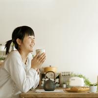 温かいお茶を飲み微笑む20代の女性の横顔