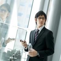 オフィスの窓辺で携帯電話を使う20代のビジネスマン
