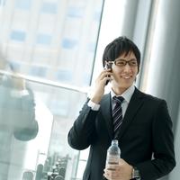 オフィスの窓辺に立ち携帯電話で話す20代のビジネスマン