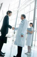 製薬会社の営業マンと握手をする医者と看護師