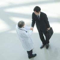 製薬会社の営業マンと握手をする医者