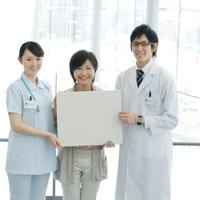 メッセージボードを持つ患者と医者と介護士