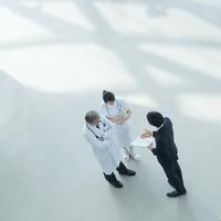 製品を売り込む製薬会社の営業マンと話を聞く医者と看護師